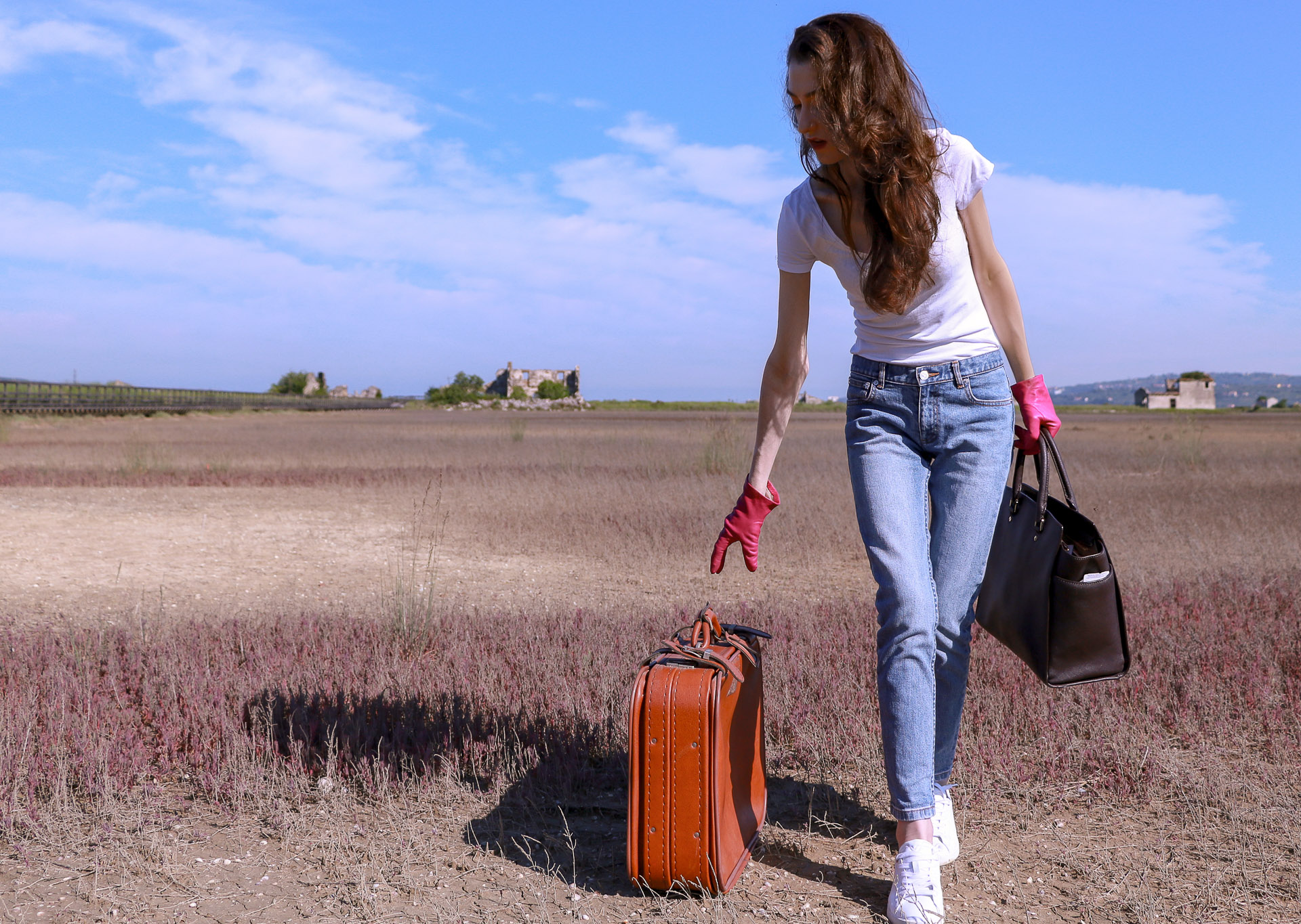 Popular fashion influencer Veronika Lipar of Brunette from Wall Street dressed in a.p.c. bleach denim jeans Diesel white sneakers white T-shirt pink leather gloves picking up Michael Kors sachets bag vintage suitcase standing in the middle of nowhere