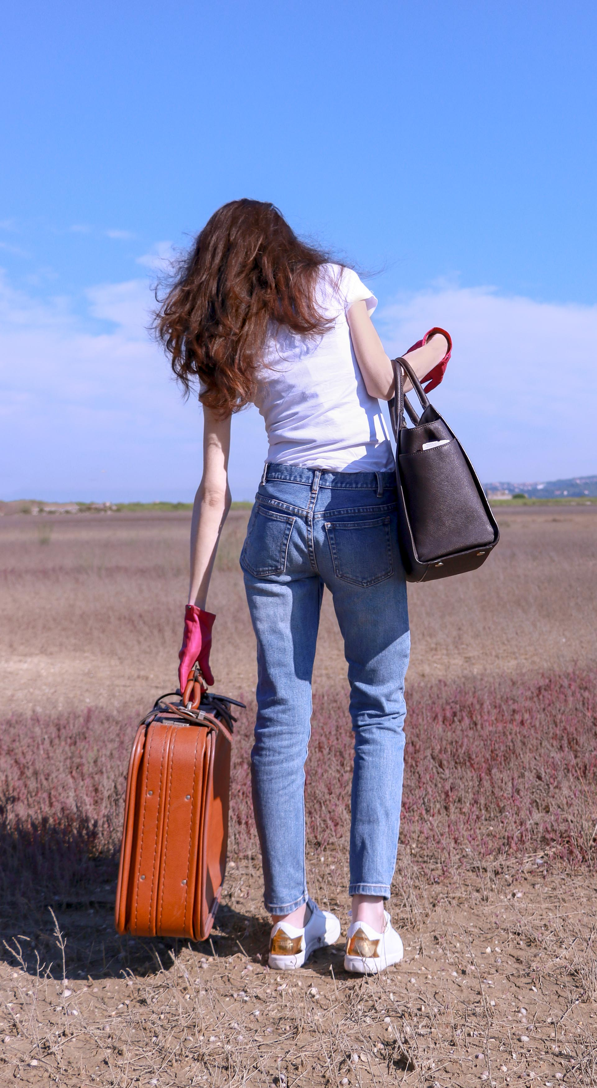 Popular fashion influencer Veronika Lipar of Brunette from Wall Street dressed in a.p.c. bleach denim jeans Diesel white sneakers white T-shirt pink leather gloves carrying Michael Kors sachets bag picking up retro suitcase standing in the middle of nowhere