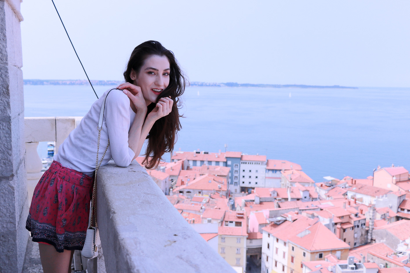 Fashion blogger Veronika Lipar of Brunette From Wall Street above the old Mediterranean seaside town wearing silk shorts, pale pink sneakers and white shoulder bag