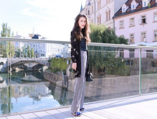 Fashion blogger Veronika Lipar of Brunette From Wall Street on the bridge over river Ljubljanica in Ljubljana, wearing dark floral shirt dress and wide-leg trousers