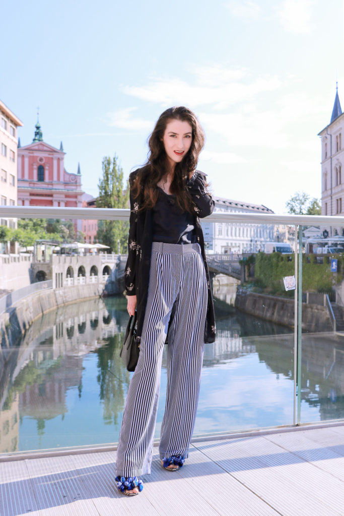 Fashion blogger Veronika Lipar of Brunette From Wall Street standing on the bridge over river Ljubljanica in Ljubljana wearing dark floral shirtdress and wide-leg pants