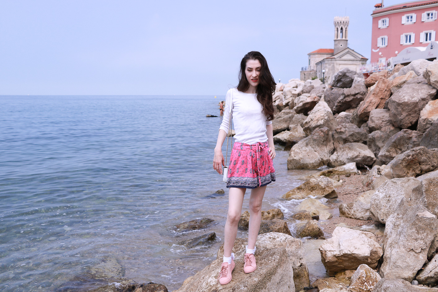 Fashion blogger Veronika Lipar of Brunette From Wall Street on the bell tower above the seaside city wearing silk shorts, pale pink sneakers and white shoulder bag