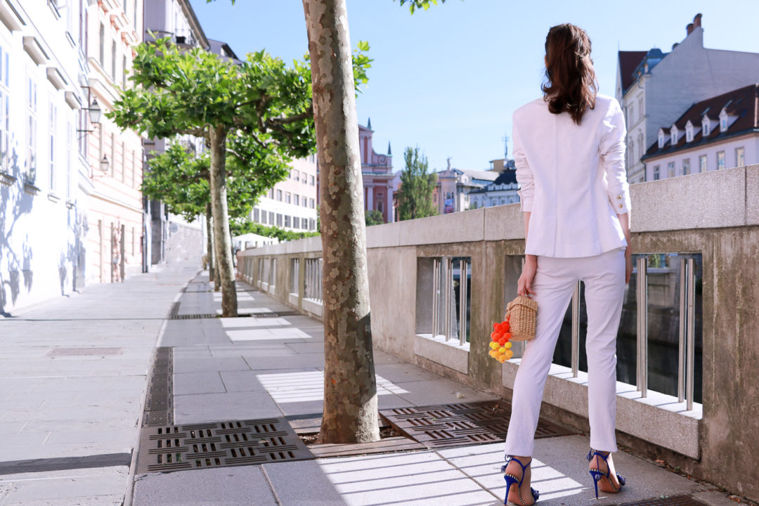 Fashion blogger Veronika Lipar of Brunette From Wall Street sharing how to wear all white pantsuit to work this summer