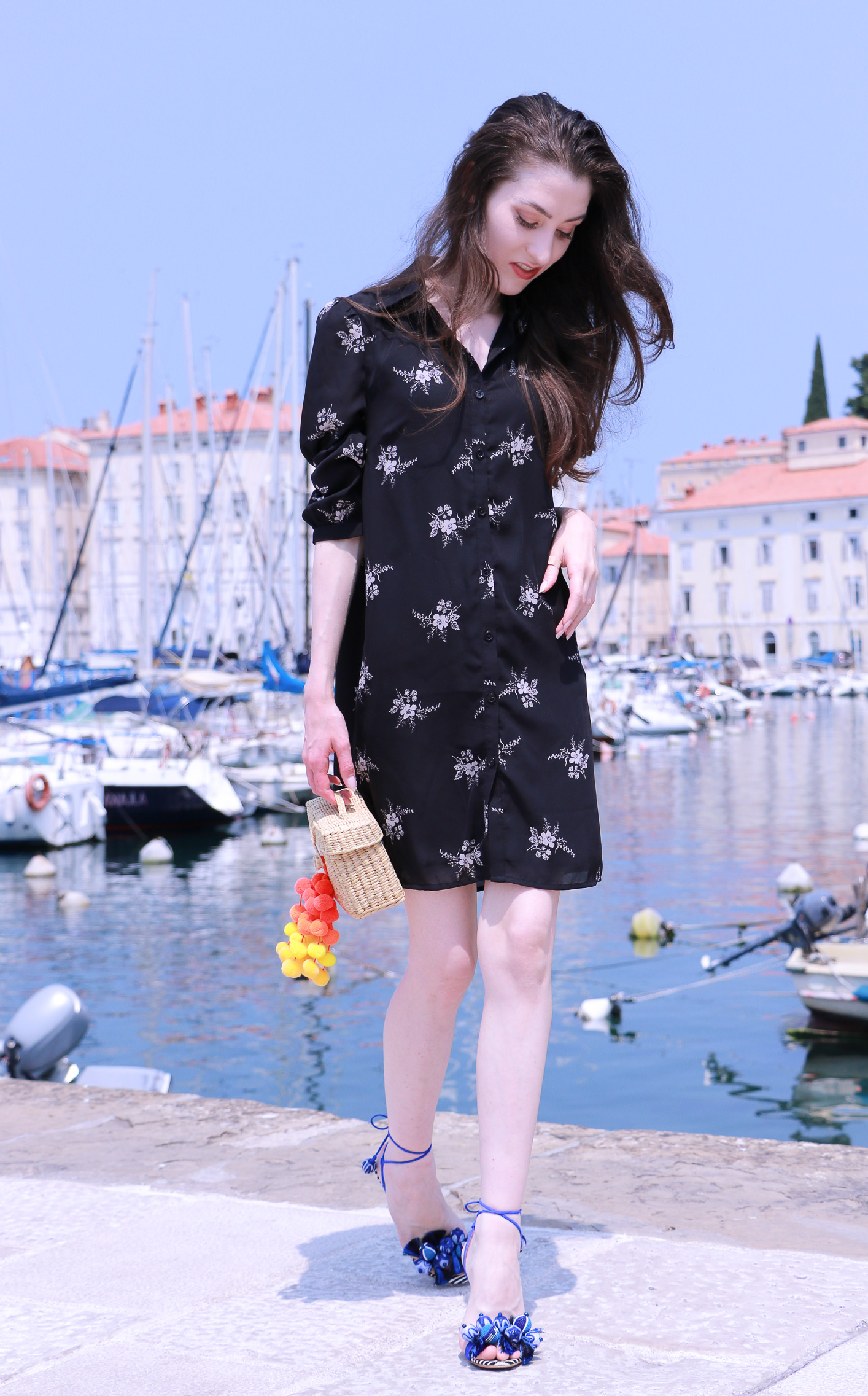 Fashion blogger Veronika Lipar of Brunette From Wall Street on her stroll through the seaside town wearing shirt dress and raffia basket bag