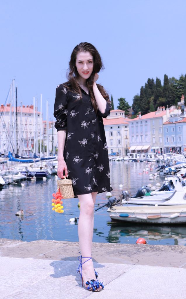 Fashion blogger Veronika Lipar of Brunette From Wall Street dressed in black summer dress and raffia basket bag in the port