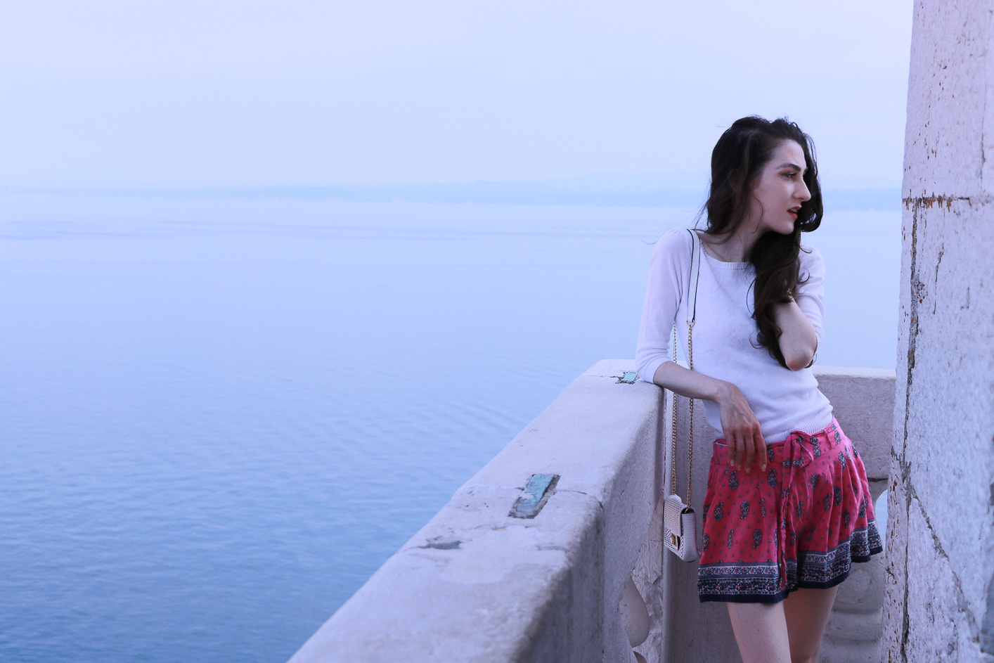 Fashion blogger Veronika Lipar of Brunette From Wall Street above the old Mediterranean seaside town dressed in silk shorts, pale pink sneakers and white shoulder bag