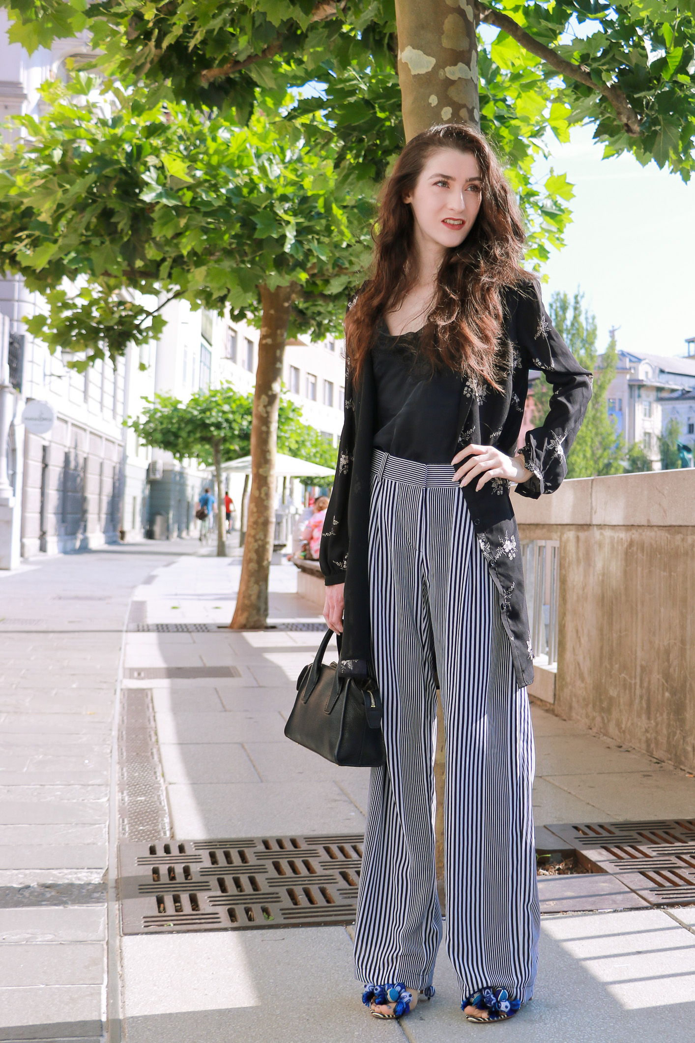 Fashion blogger Veronika Lipar of Brunette From Wall Street sharing how to style layers in the summer, wearing dark floral shirtdress and wide-leg pants