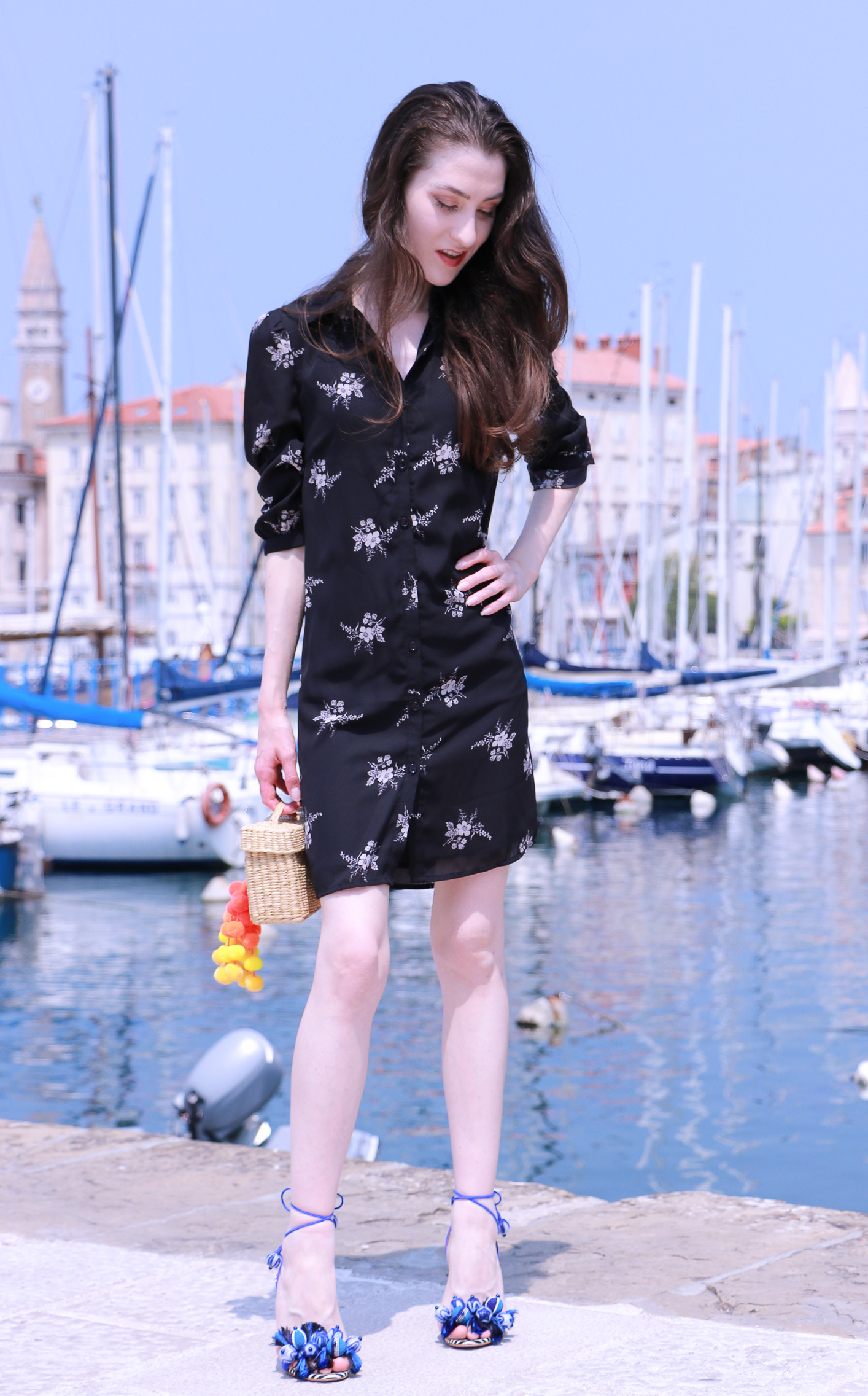 Fashion blogger Veronika Lipar of Brunette From Wall Street sharing how to look chic on summer vacations wearing floral dress, raffia basket bag and sandals