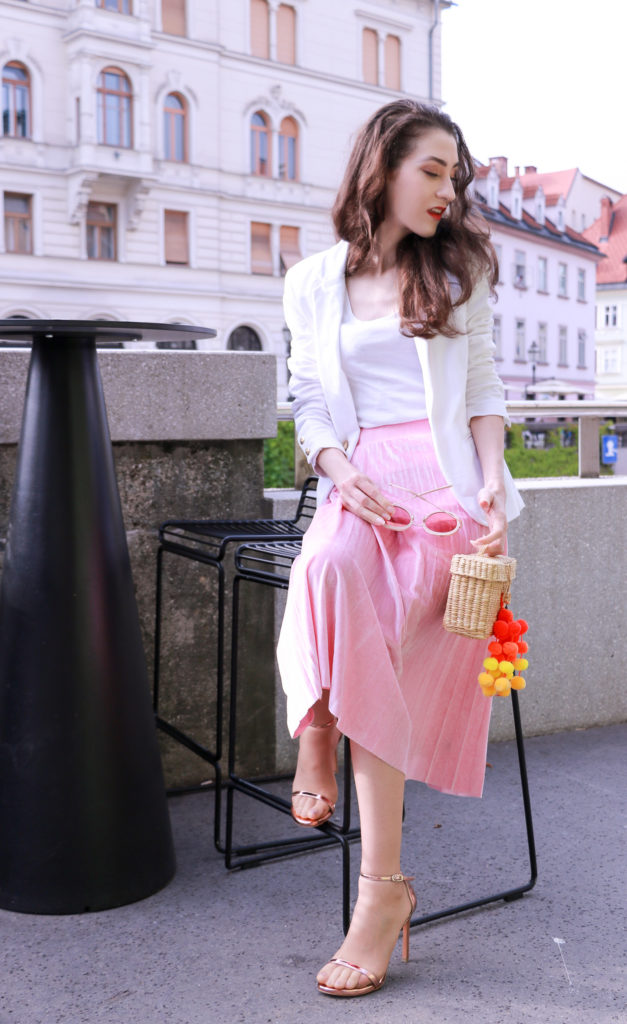 Fashion blogger Veronika Lipar of Brunette From Wall Street answering 5 questions about her, wearing pink midi skirt, Sunday Somewhere round sunglasses, metallic sandals from Stuart Weitzman, and raffia basket bag from Nannancay