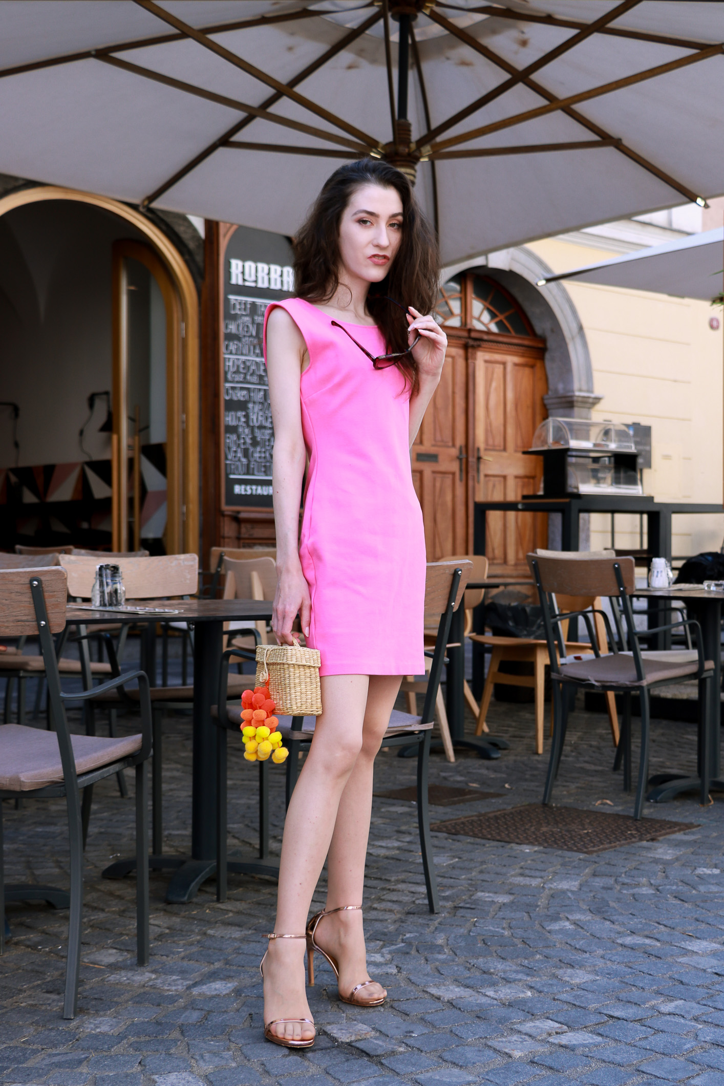 Fashion blogger Veronika Lipar of Brunette From Wall Street sharing how to style pink cocktail dress, rose gold sandals and raffia bag this summer