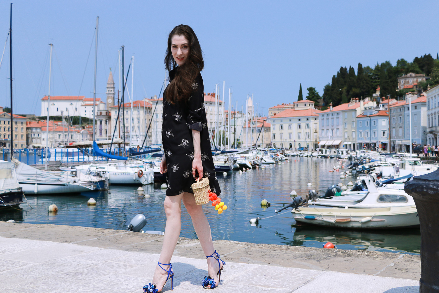Fashion blogger Veronika Lipar of Brunette From Wall Street wearing dark floral dress and raffia basket bag in the seaside town
