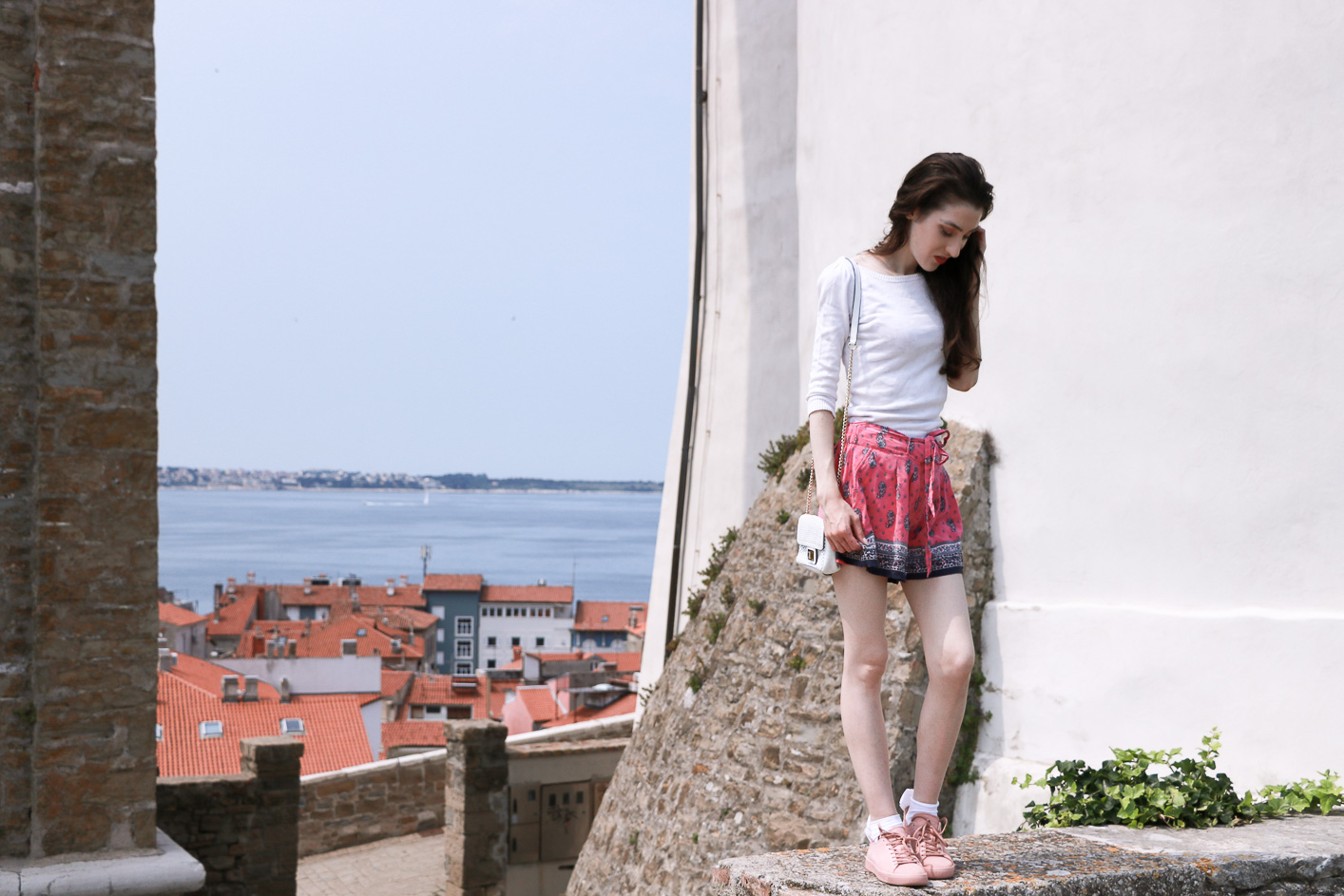 Fashion blogger Veronika Lipar of Brunette From Wall Street on her Sunday trip to Piran Slovenia wearing silk shorts, pale pink sneakers and white shoulder bag