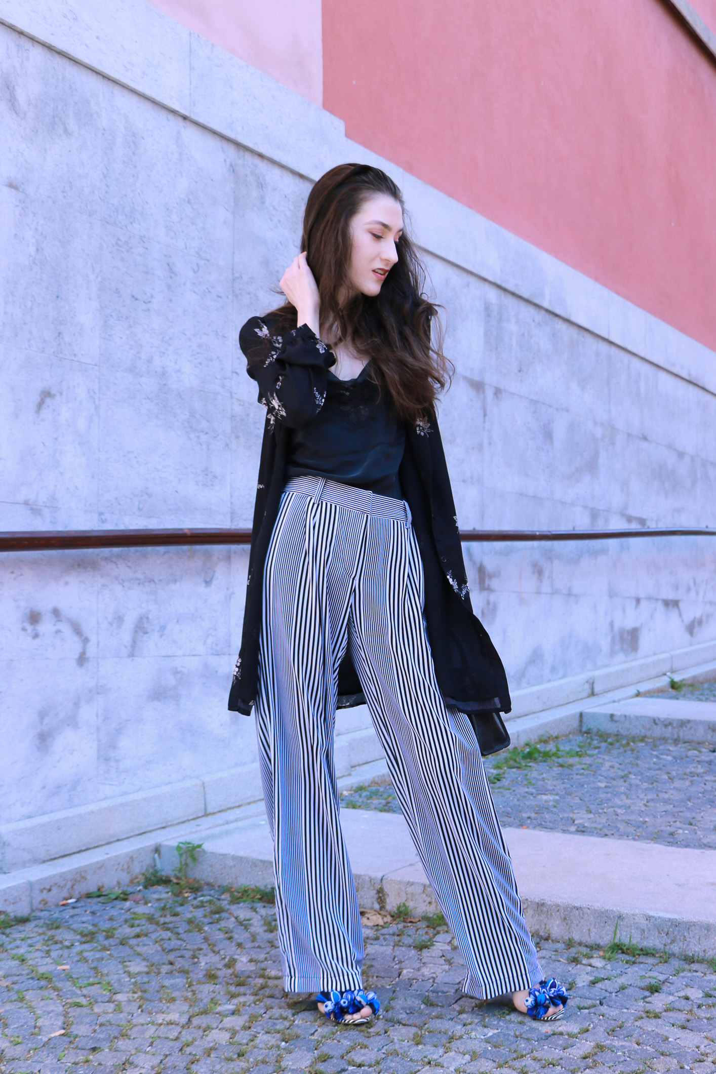 Fashion blogger Veronika Lipar of Brunette From Wall Street sharing how to style long layers for a chic summer look, wearing dark floral shirtdress and wide-leg trousers