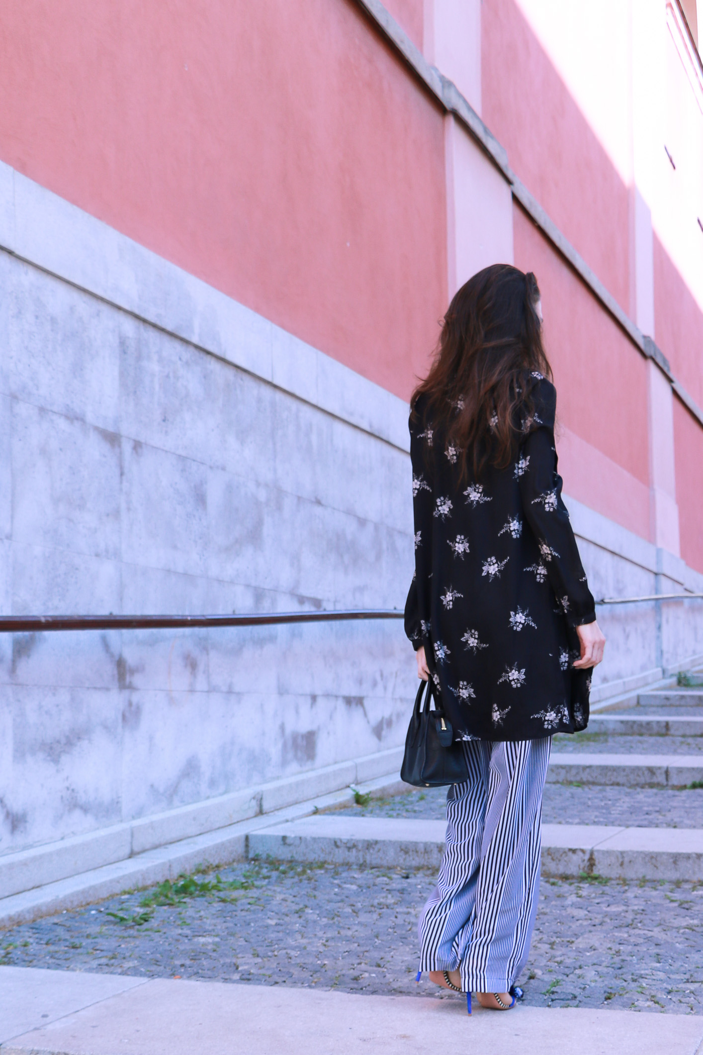 Fashion blogger Veronika Lipar of Brunette From Wall Street sharing how to do layering this summer wearing dark floral shirt dress and wide-leg pants