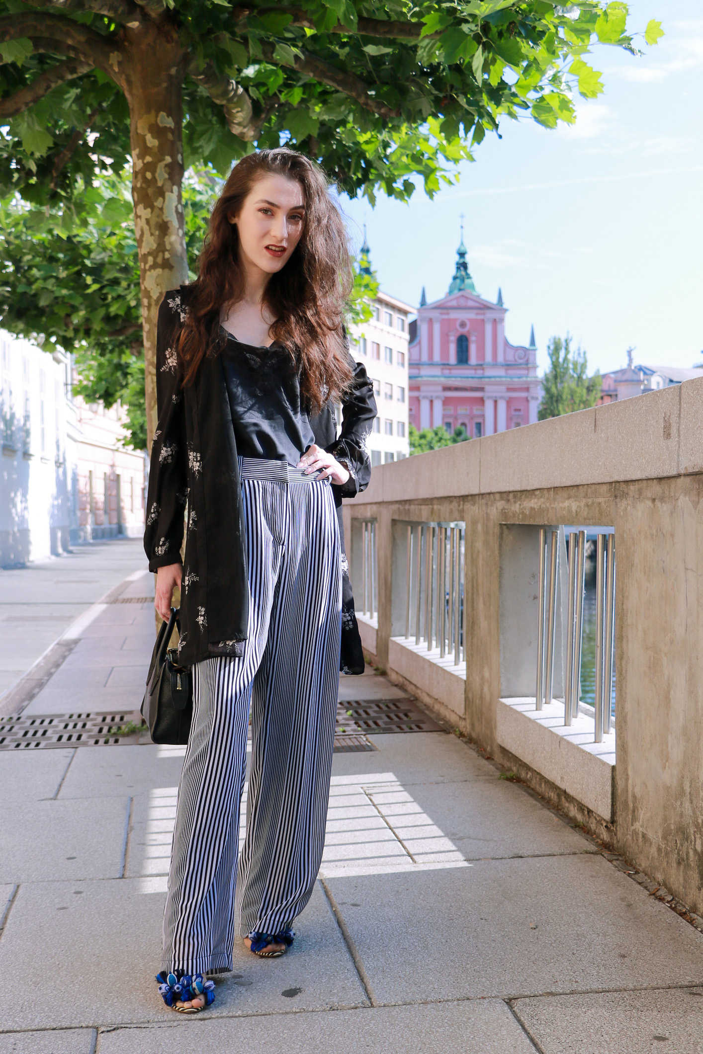 Fashion blogger Veronika Lipar of Brunette From Wall Street sharing how to style layers in the summer, wearing dark floral shirt dress and wide-leg trousers