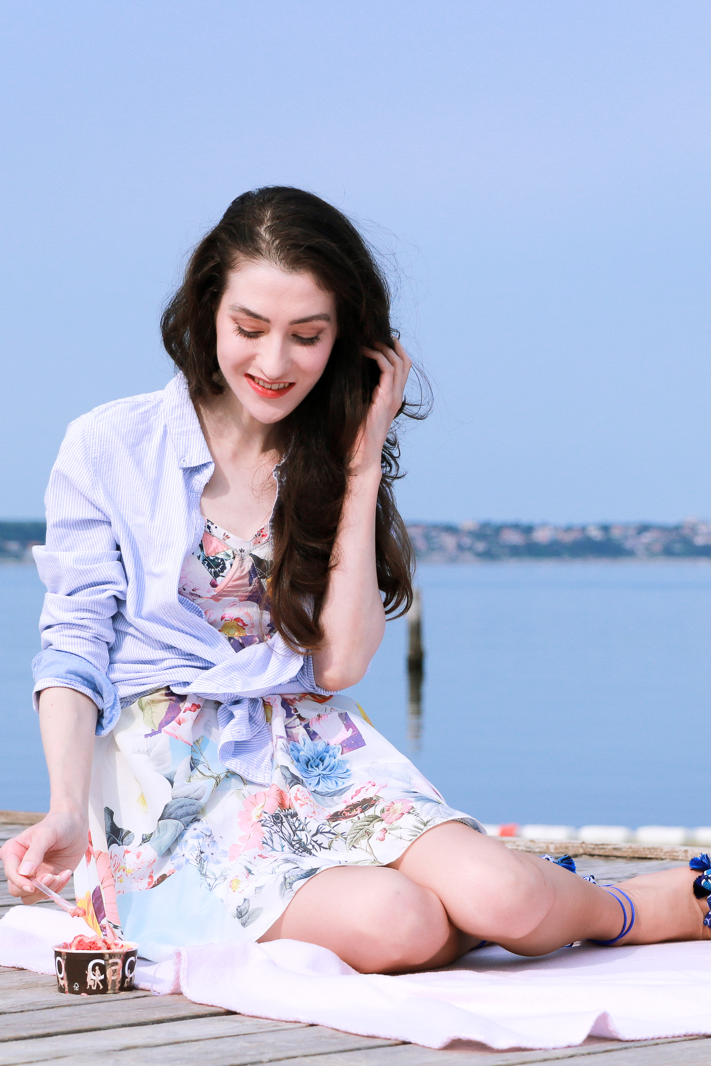 Fashion blogger Veronika Lipar of Brunette From Wall Street on her first summer picnic on the beach eating ice cream on the pink picnic blanket wearing floral summer dress, a shirt with a knot and raffia basket bag