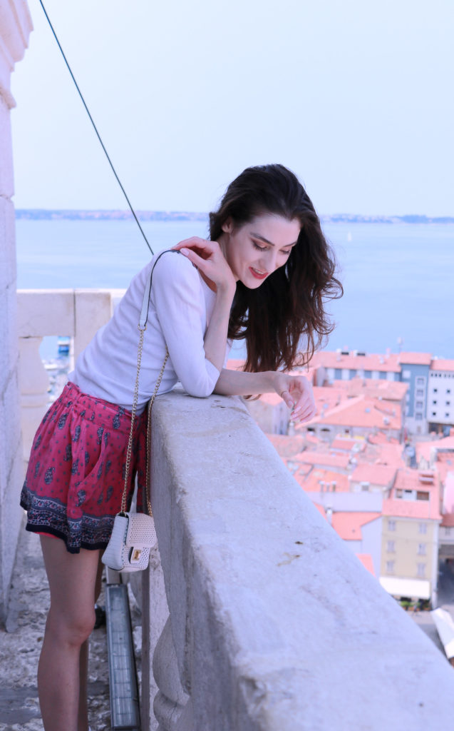 Fashion blogger Veronika Lipar of Brunette From Wall Street on the bell tower above the old Mediterranean seaside town wearing silk shorts, pale pink sneakers and white shoulder bag