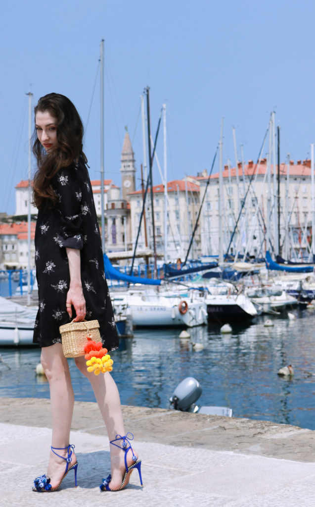Fashion blogger Veronika Lipar of Brunette From Wall Street wearing shirt dress, raffia basket bag and blue sandals in the old port