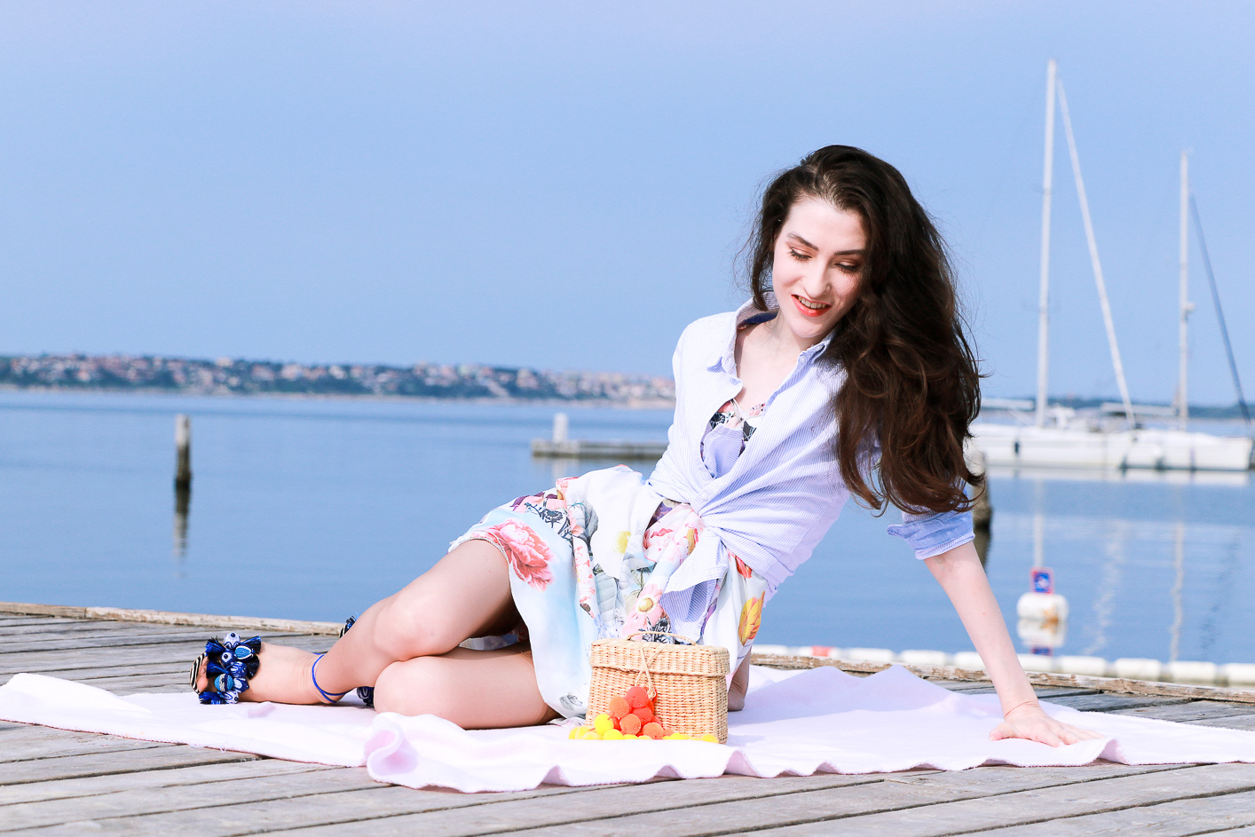 Fashion blogger Veronika Lipar of Brunette From Wall Street having first summer picnic on the seaside wearing floral summer dress, a shirt with a knot and raffia basket bag