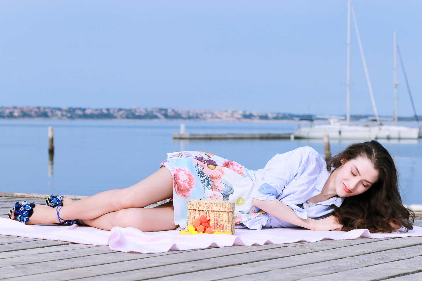 Fashion blogger Veronika Lipar of Brunette From Wall Street having first summer picnic on the beach wearing floral summer dress, a shirt with a knot and raffia basket bag
