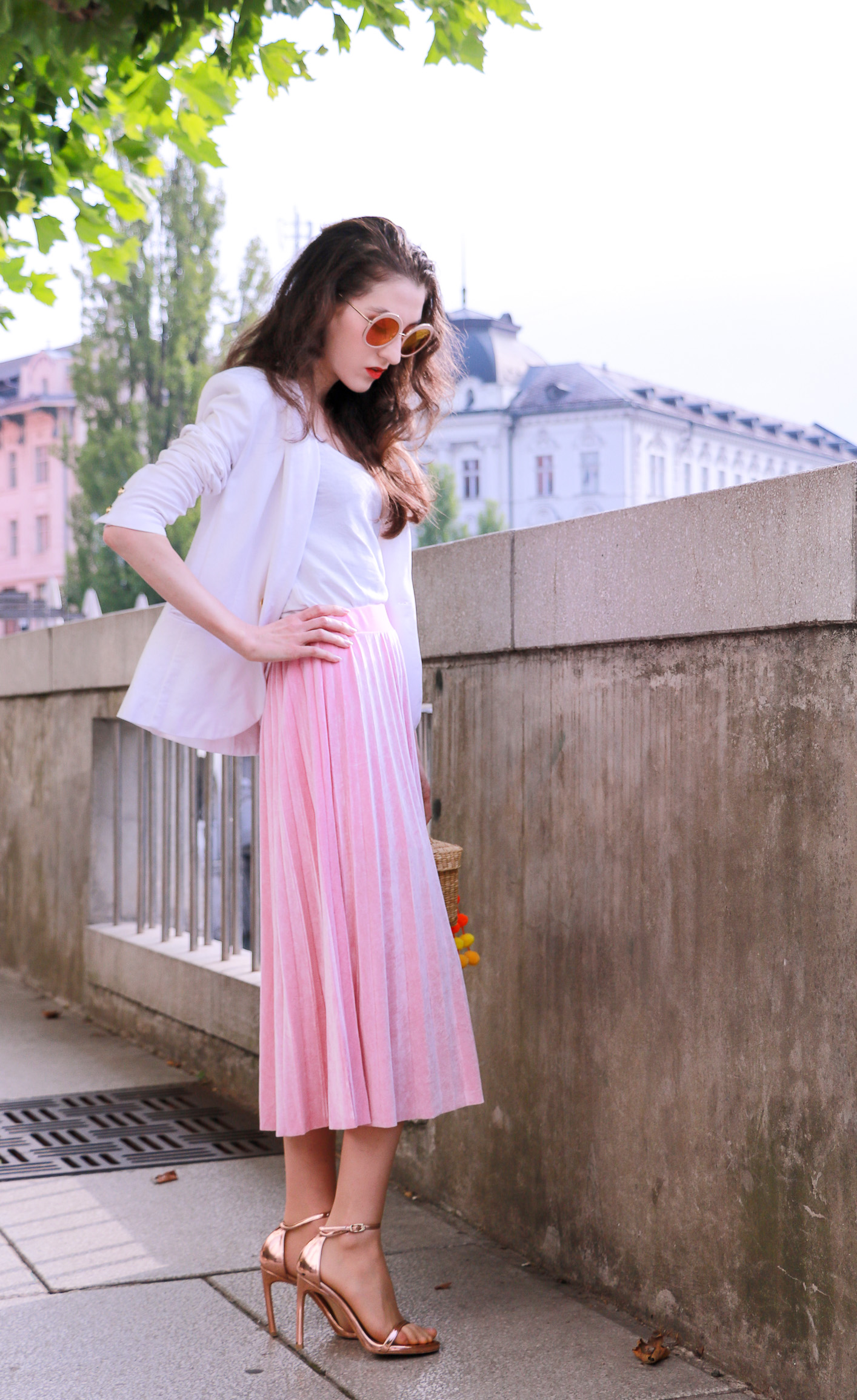 Fashion blogger Veronika Lipar of Brunette From Wall Street wearing chic pink midi skirt with pleats, Sunday Somewhere round sunglasses, metallic sandals from Stuart Weitzman, and raffia basket bag from Nannancay