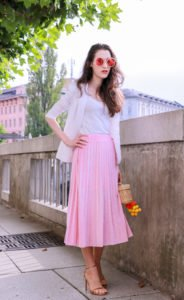 Fashion blogger Veronika Lipar of Brunette From Wall Street dressed in chic pink pleated midi skirt, Sunday Somewhere round sunglasses, metallic sandals from Stuart Weitzman, and raffia basket bag from Nannancay