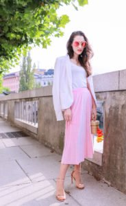 Fashion blogger Veronika Lipar of Brunette From Wall Street answering 5 questions about her, dressed in pink midi skirt, Sunday Somewhere round sunglasses, metallic sandals from Stuart Weitzman, and raffia basket bag from Nannancay