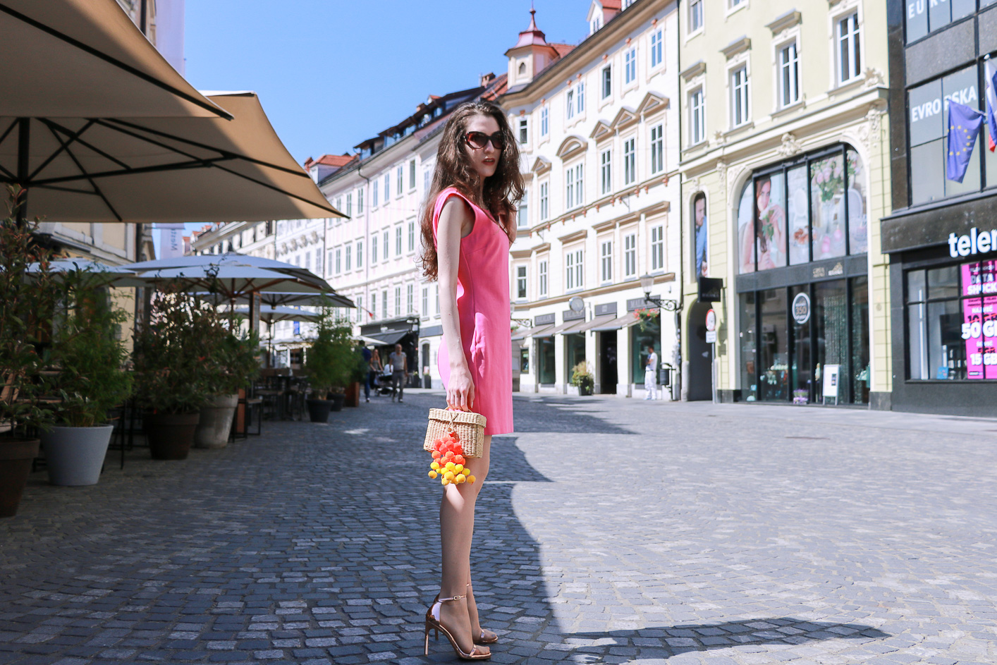 Fashion blogger Veronika Lipar of Brunette From Wall Street sharing how to wear pink cocktail dress, rose gold sandals and raffia bag this summer