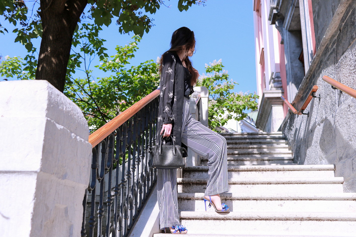 Fashion blogger Veronika Lipar of Brunette From Wall Street standing on the stairs in Ljubljana, wearing dark floral shirtdress and wide-leg trousers