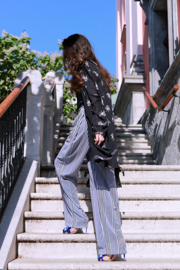 Fashion blogger Veronika Lipar of Brunette From Wall Street standing climbing the stairs in Ljubljana, wearing dark floral shirtdress and wide-leg trousers