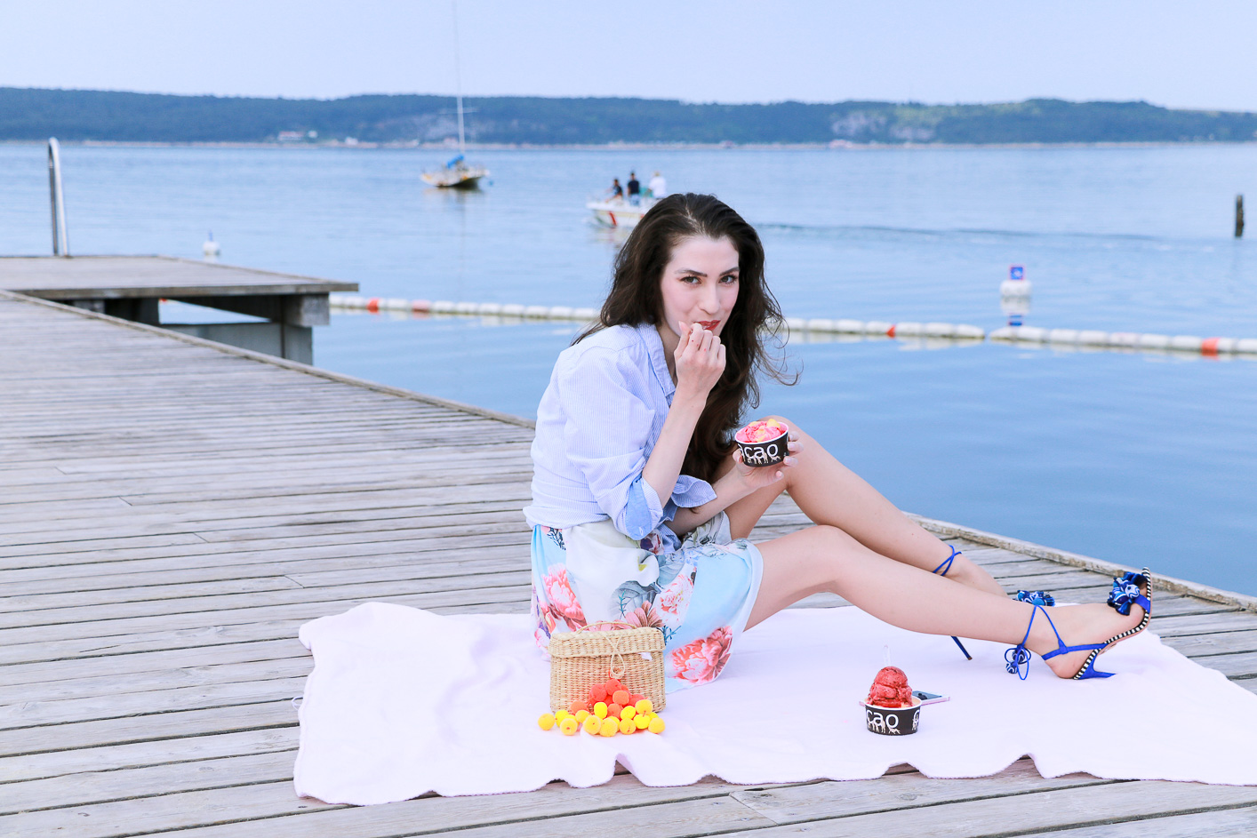 Fashion blogger Veronika Lipar of Brunette From Wall Street having first summer picnic on the wooden pier wearing floral summer dress, a shirt with a knot and raffia basket bag