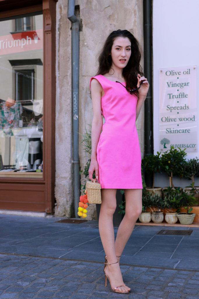 Fashion blogger Veronika Lipar of Brunette From Wall Street looking like a Barbie wearing pink cocktail dress, rose gold sandals and raffia bag in Ljubljana