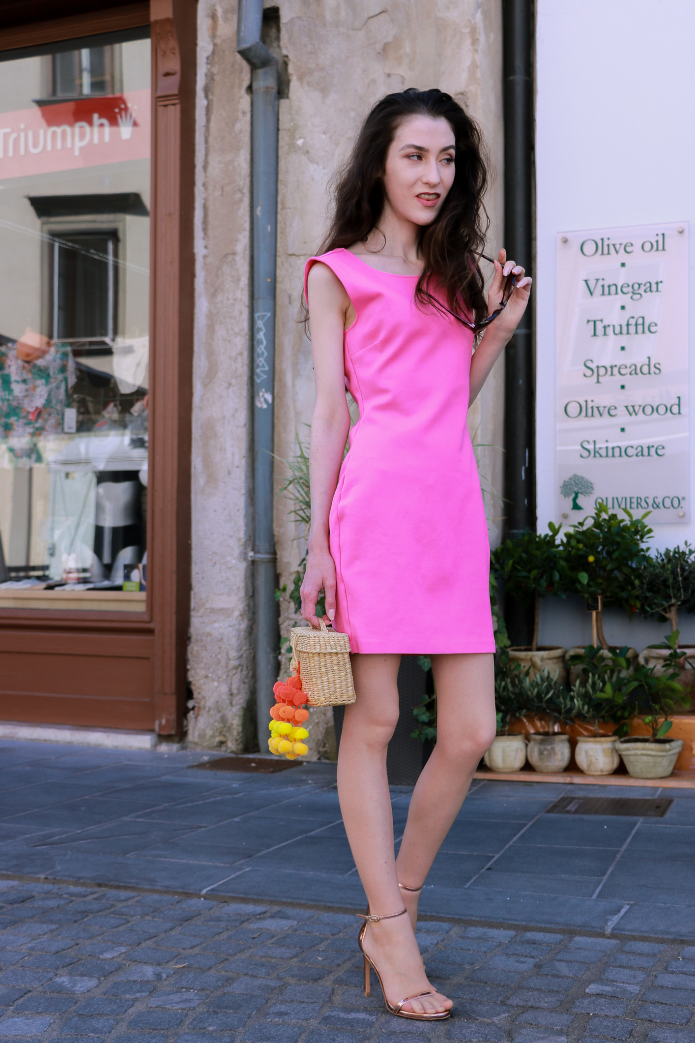 Fashion blogger Veronika Lipar of Brunette From Wall Street looking like a Barbie dressed in pink cocktail dress, rose gold sandals and raffia bag in Ljubljana