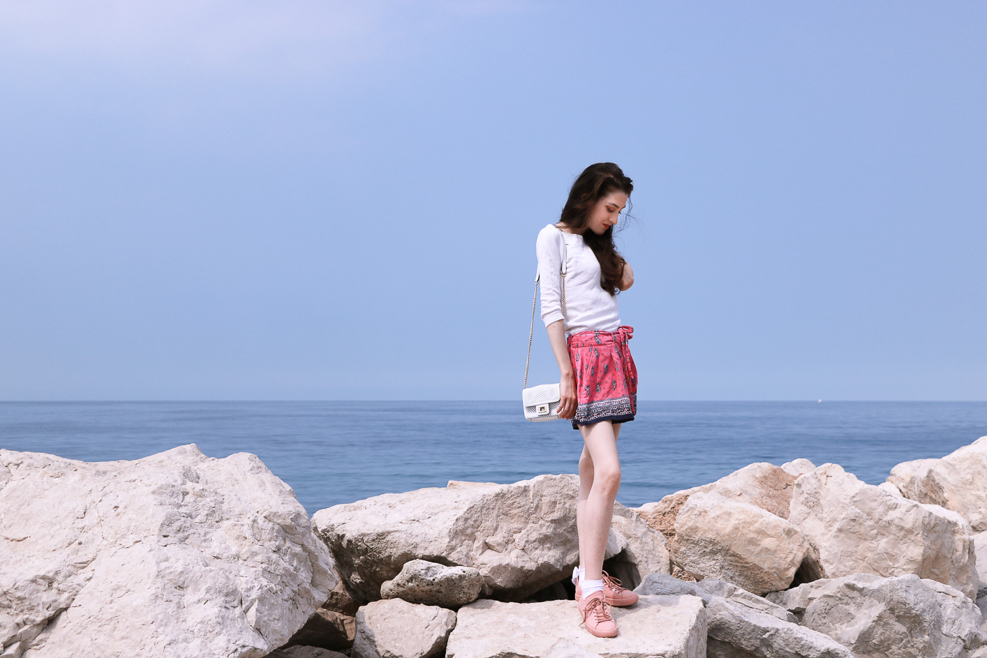 Fashion blogger Veronika Lipar of Brunette From Wall Street on her Sunday trip to Piran Slovenia dressed in silk shorts, pale pink sneakers and white shoulder bag