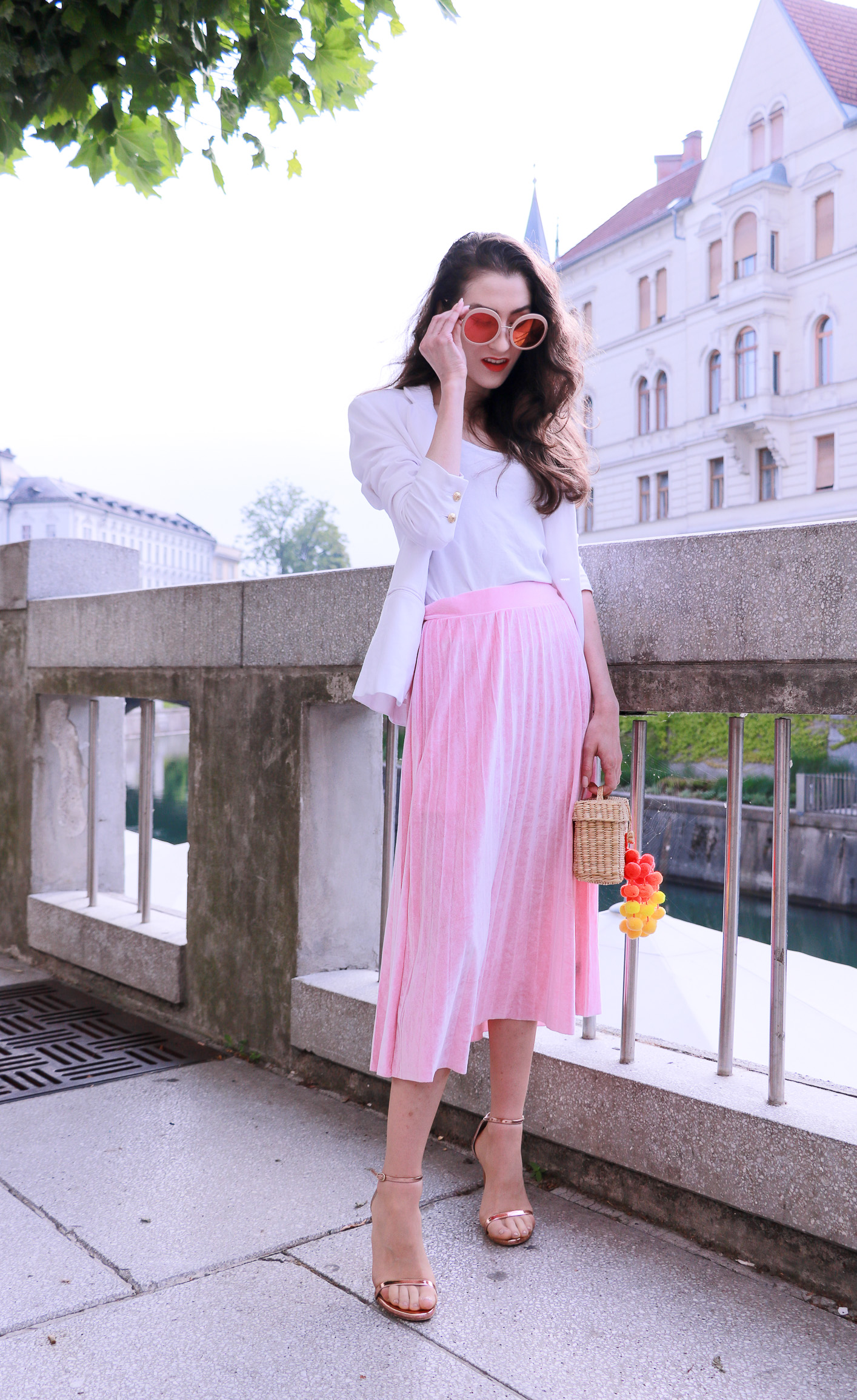 Fashion blogger Veronika Lipar of Brunette From Wall Street answering 5 questions about her, wearing pink midi skirt, Sunday Somewhere round sunglasses, metallic sandals from Stuart Weitzman