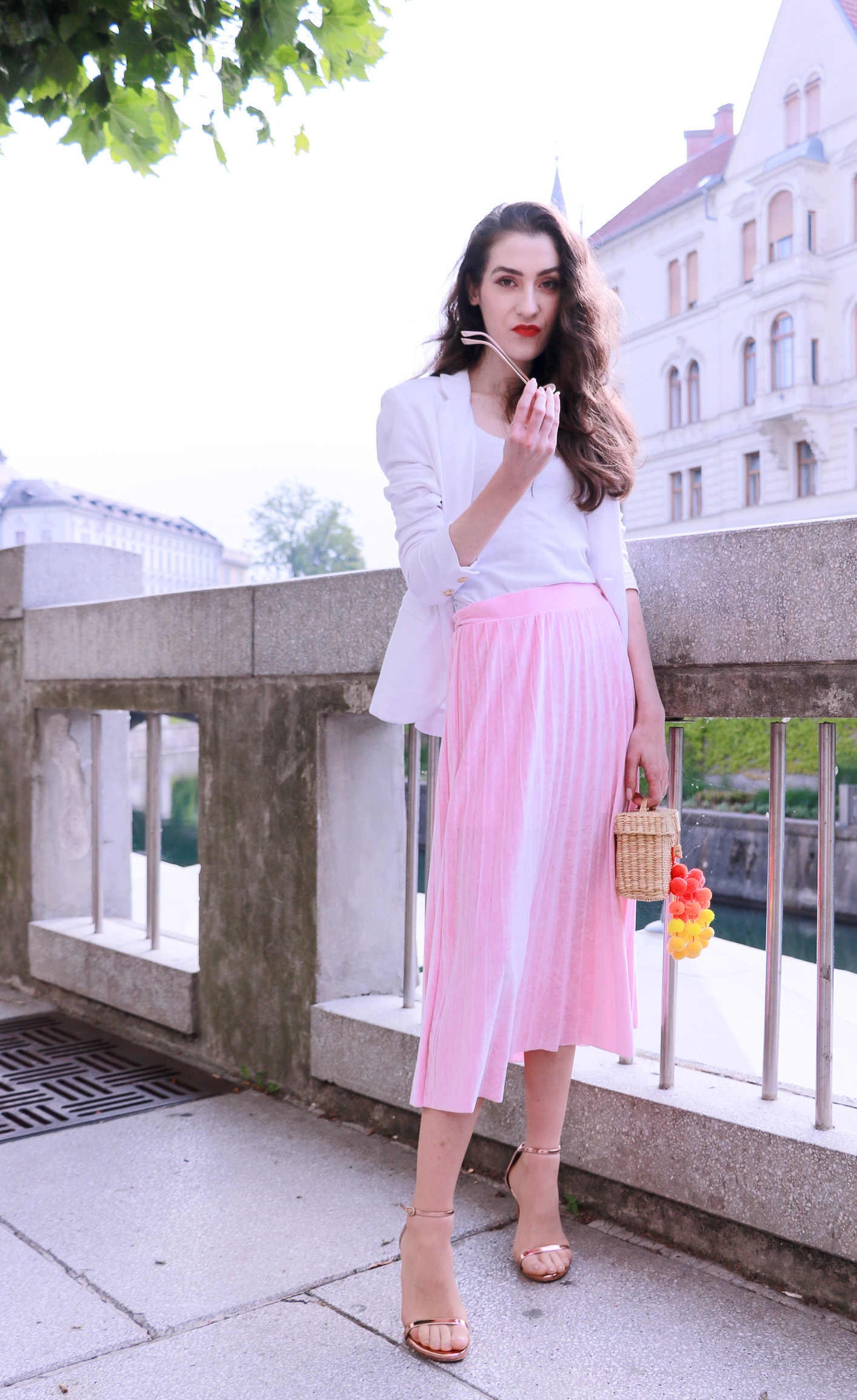 Fashion blogger Veronika Lipar of Brunette From Wall Street dressed in chic pink midi skirt with pleats, Sunday Somewhere round sunglasses, metallic sandals from Stuart Weitzman, and raffia basket bag from Nannancay