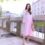 Fashion blogger Veronika Lipar of Brunette From Wall Street wearing chic pink pleated midi skirt, Sunday Somewhere round sunglasses, metallic sandals from Stuart Weitzman, and raffia basket bag from Nannancay