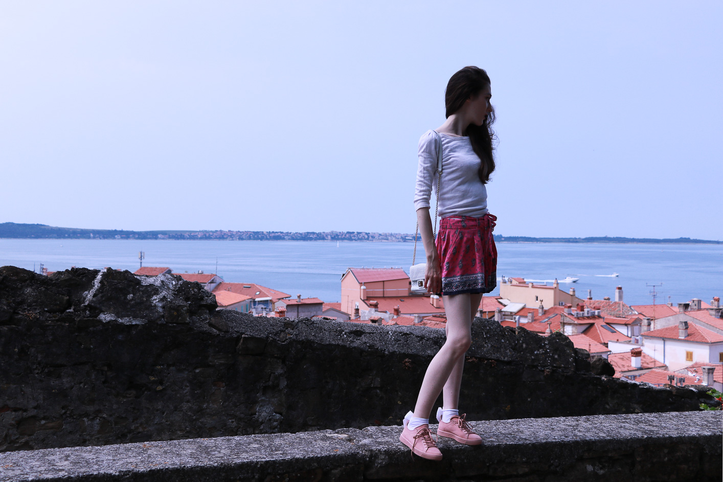 Fashion blogger Veronika Lipar of Brunette From Wall Street on her summer vacation in Piran Slovenia wearing silk shorts, pale pink sneakers and white shoulder bag