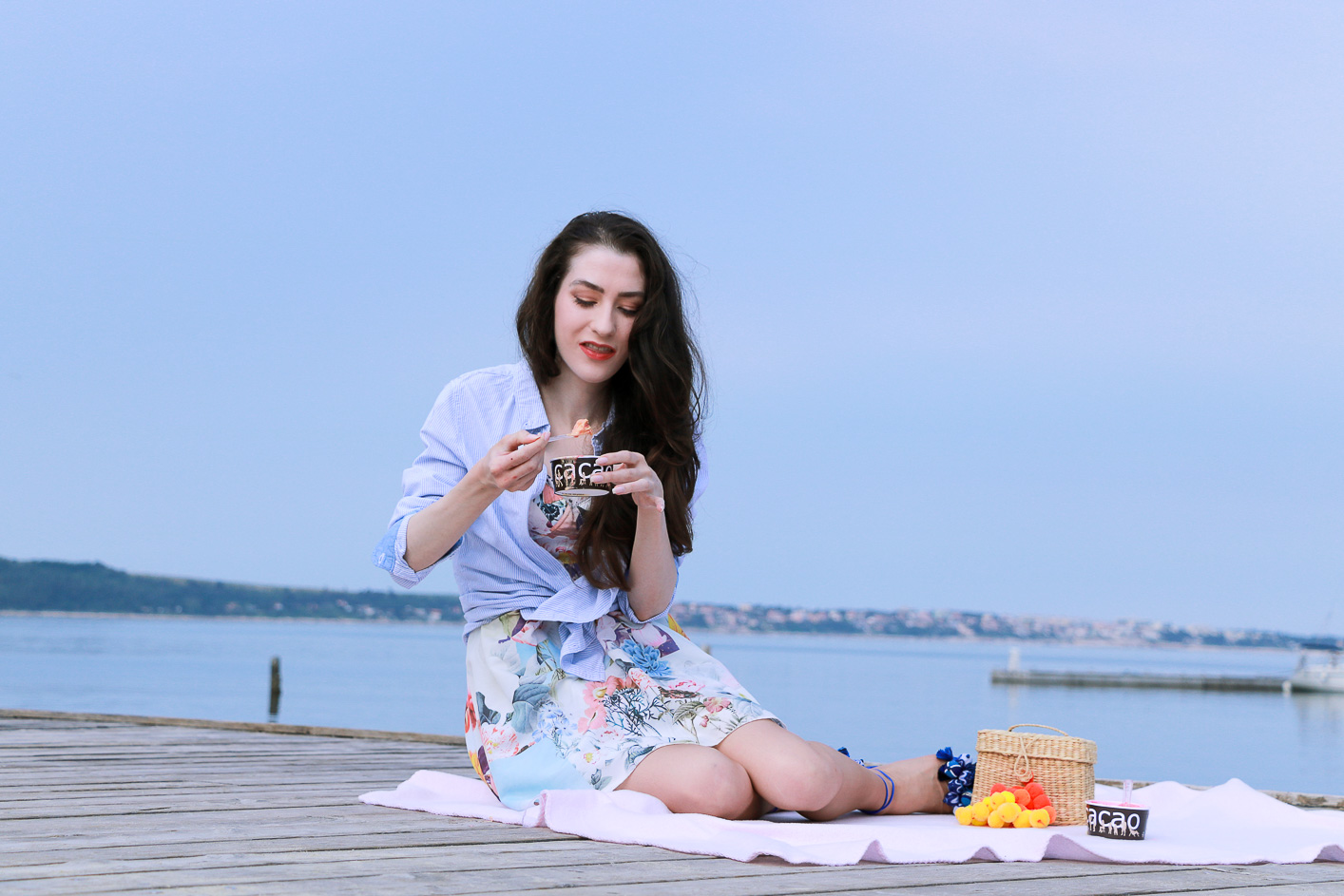 Fashion blogger Veronika Lipar of Brunette From Wall Street on her first summer picnic by the Adriatic sea eating ice cream on the pink picnic blanket wearing floral summer dress, a shirt with a knot and raffia basket bag
