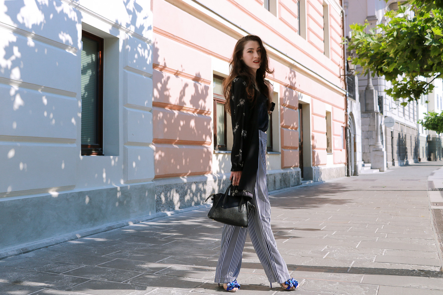 Fashion blogger Veronika Lipar of Brunette From Wall Street sharing how to style layers in the summer, wearing dark floral shirt dress and wide-leg pants