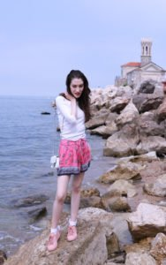 Fashion blogger Veronika Lipar of Brunette From Wall Street standing on the rocks by the Adriatic Sea wearing silk shorts, pale pink sneakers and white shoulder bag