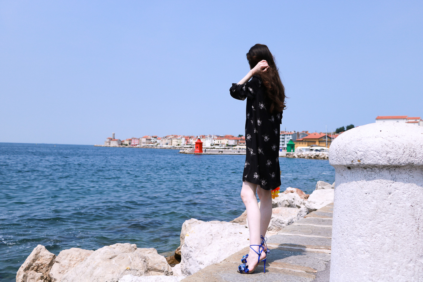 Fashion blogger Veronika Lipar of Brunette From Wall Street wearing chic dark floral shirt dress by the sea