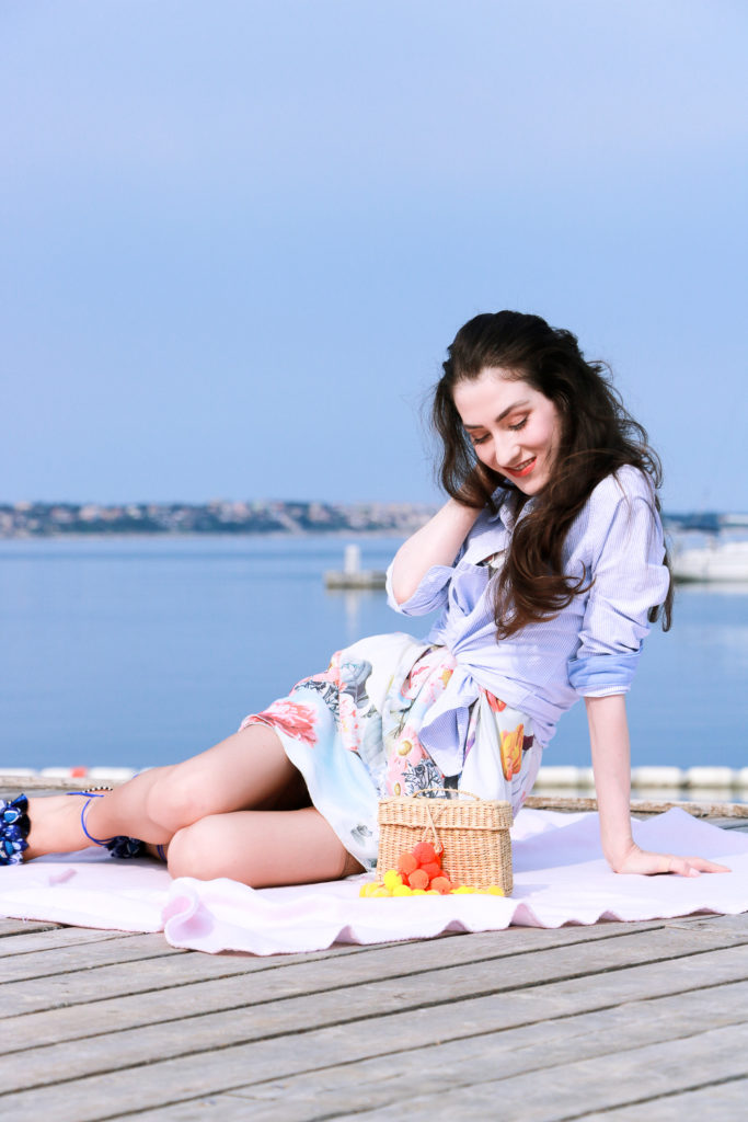 Fashion blogger Veronika Lipar of Brunette From Wall Street having first summer picnic by the sea wearing floral summer dress, a shirt with a knot and raffia basket bag