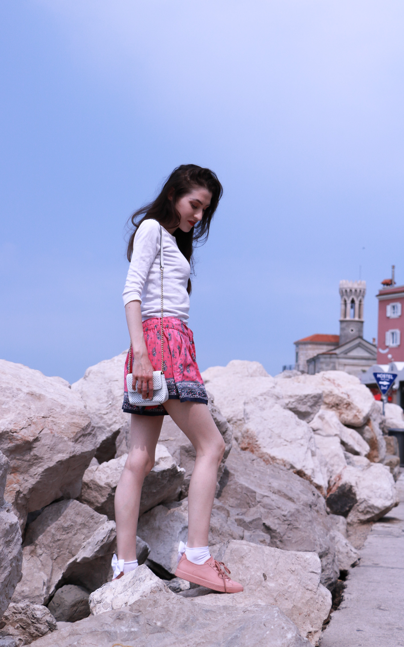 Fashion blogger Veronika Lipar of Brunette From Wall Street on her summer vacation in Piran Slovenia dressed in silk shorts, pale pink sneakers and white shoulder bag