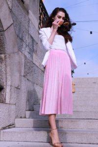 Fashion blogger Veronika Lipar of Brunette From Wall Street answering 5 questions about her, dressed in pink midi skirt, Sunday Somewhere round sunglasses, metallic sandals from Stuart Weitzman