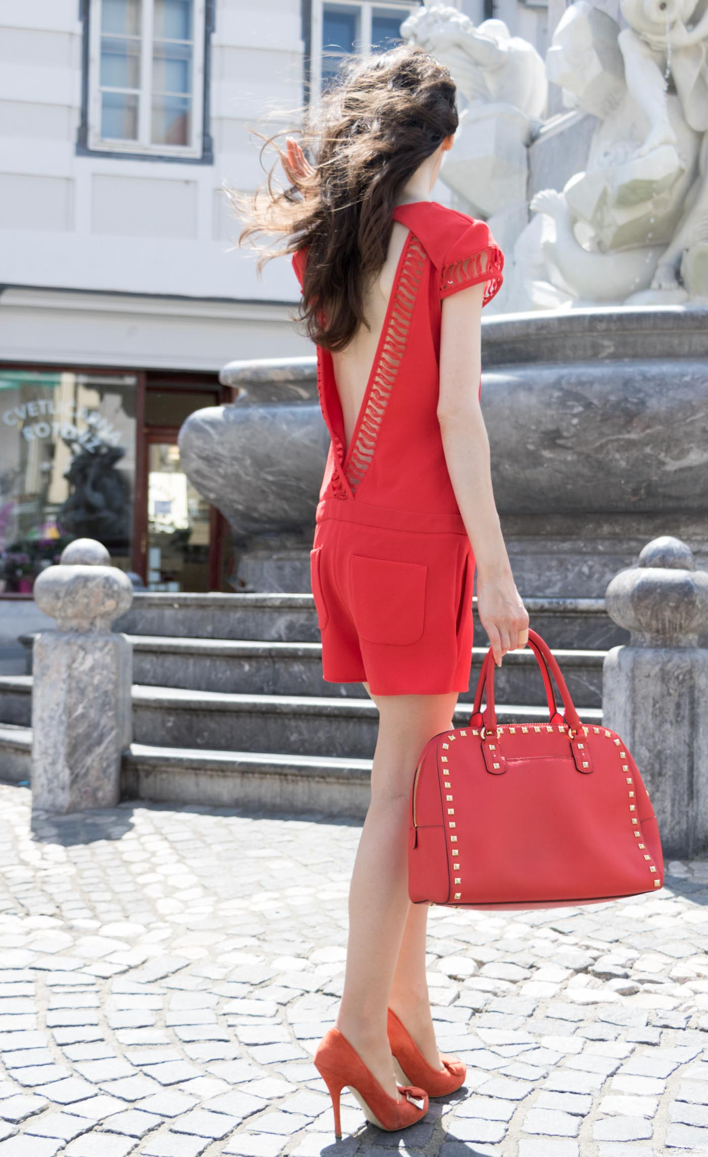 Fashion Blogger Veronika Lipar of Brunette from Wall Street wearing red romper with the open back, red heels and red Michael Kors tote bag in the city