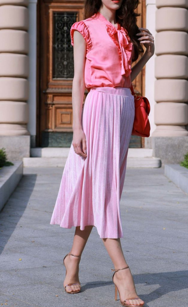Fashion Blogger Veronika Lipar of Brunette from Wall Street wearing round pink sunglasses from Sunday Somewhere, pink pleated midi skirt, pink top, hot pink top handle bag and metallic rose gold sandals