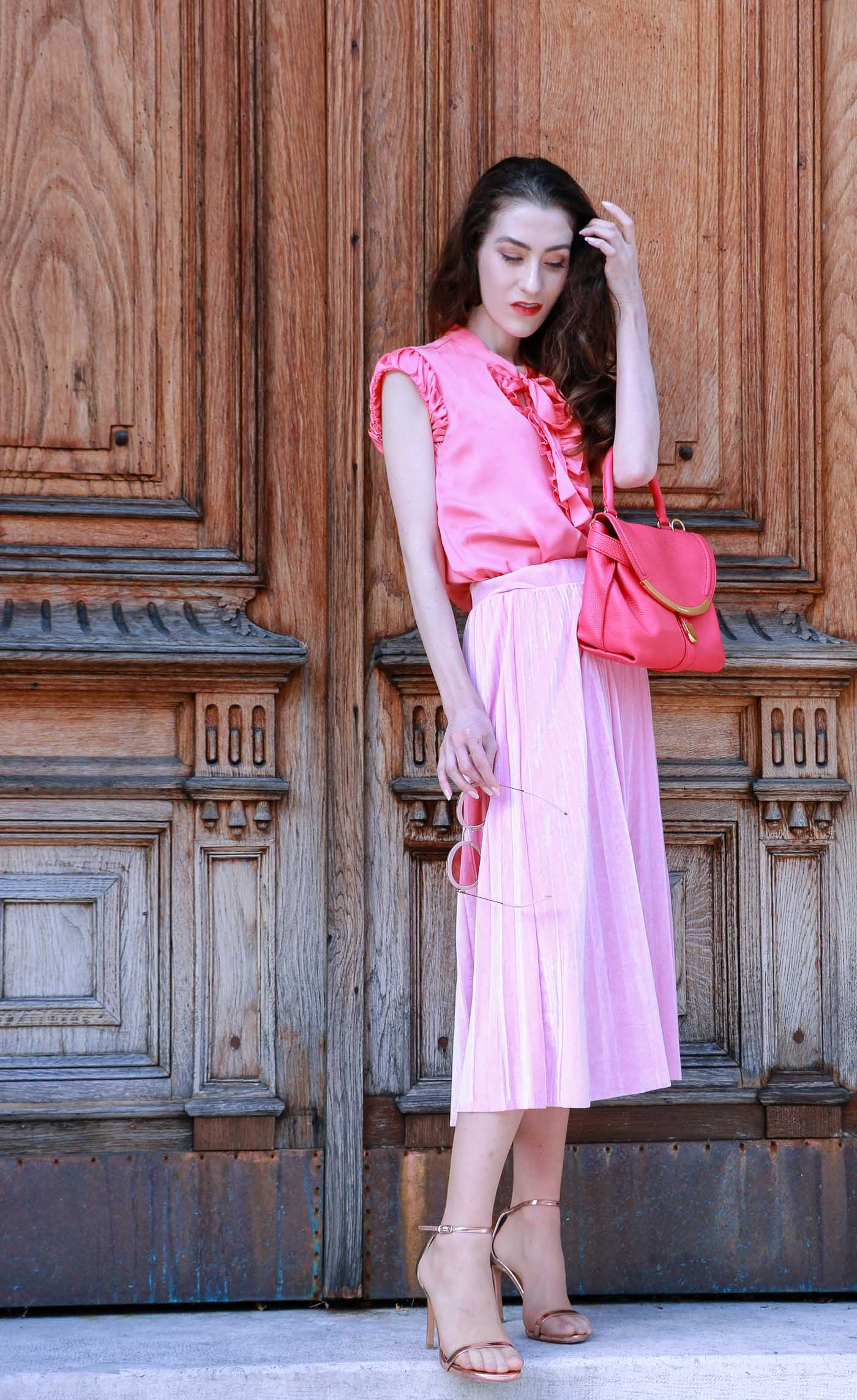 Fashion Blogger Veronika Lipar of Brunette from Wall Street wearing monochrome pink outfit while standing at the door