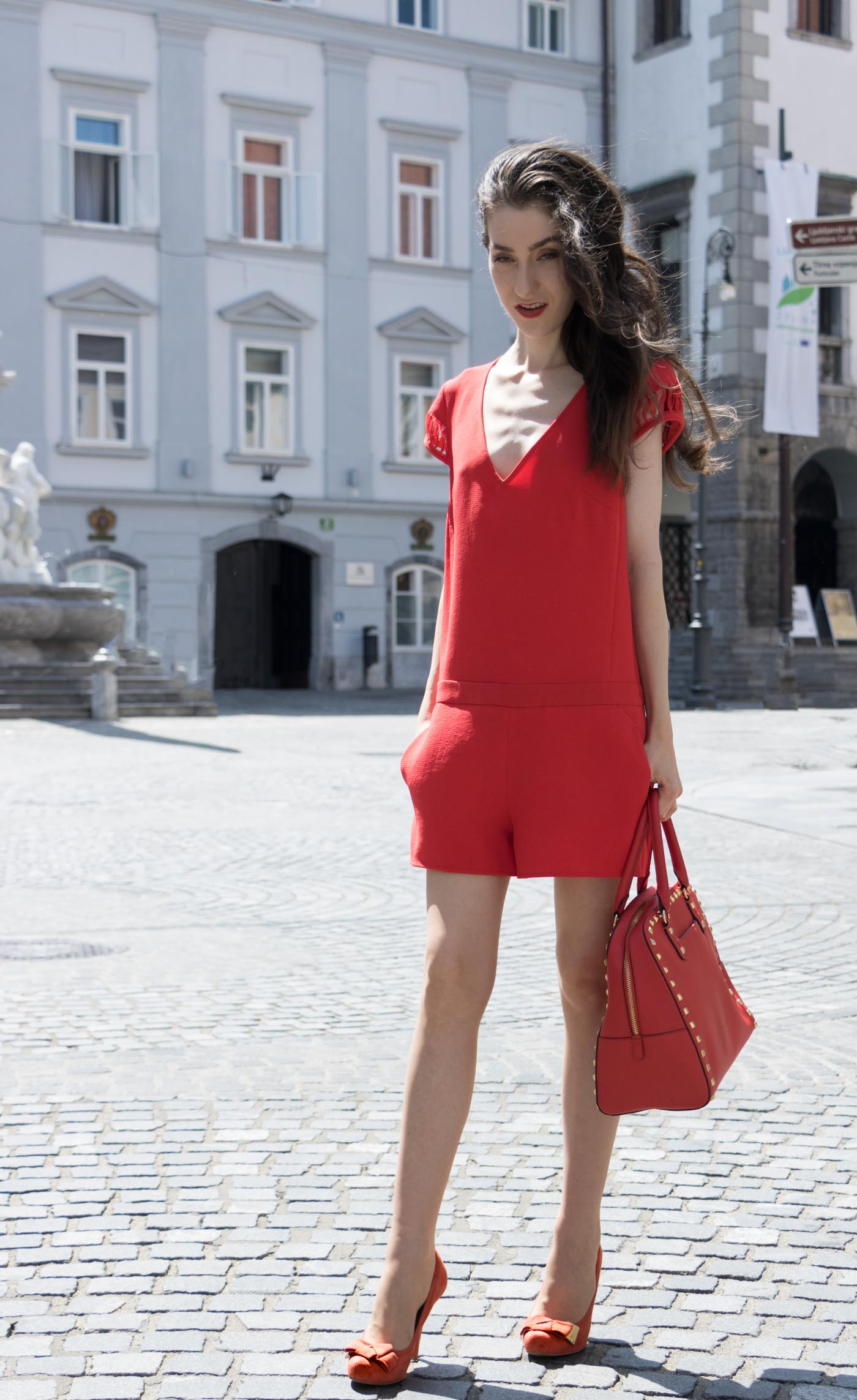 Fashion Blogger Veronika Lipar of Brunette from Wall Street wearing red romper with the open back, red heels and red Michael Kors tote bag