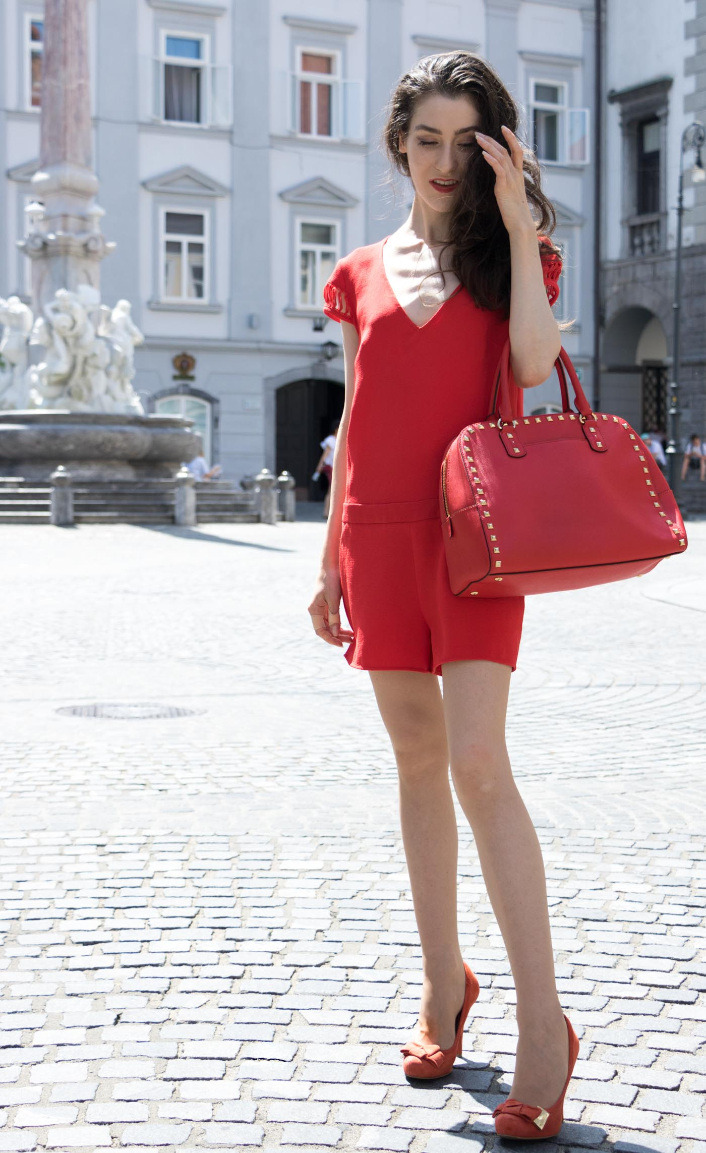 Fashion Blogger Veronika Lipar of Brunette from Wall Street wearing red romper with the open back, red pumps and red Michael Kors tote bag in Ljubljana